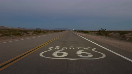 locatie : Schemer rijden over Route 66 stoep bord in de Mojave-woestijn in Zuid-Californië. Stockvideo