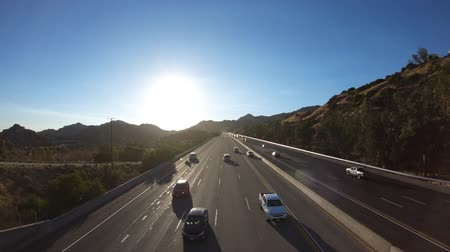 údolí : Slow motion view of the 118 freeway traffic in the Santa Susana Pass area of the San Fernando Valley in Los Angeles, California.
