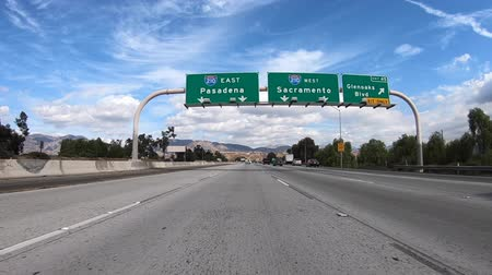 rampa : Slow motion driving shot of Pasadena and Sacramento overhead highway signs at the 118 and 210 freeway interchange in Los Angeles, California. Vídeos