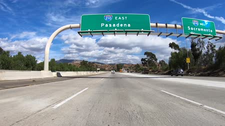 rampa : Slow motion driving shot of Pasadena and Sacramento overhead highway signs in the San Fernando Valley area of Los Angeles, California.