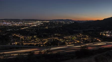 пригород : Dusk to night time lapse view of the 118 freeway near Topanga Canyon Bl in the San Fernando Valley area of Los Angeles, California.
