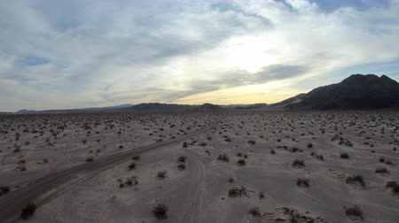 Late afternoon aerial view of empty Mojave desert landscape between Barstow and Baker in Southern California. Stok Video