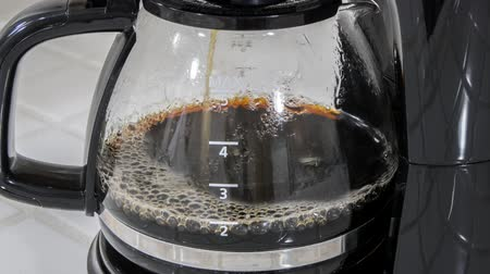 Coffee machine filling pot time lapse with zoom out.