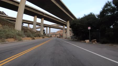 Driving under the 5 and 14 freeway interchange bridges in the Newhall Pass near Los Angeles, California. Stok Video