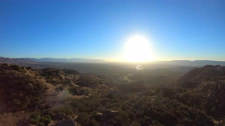 проходить : Los Angeles San Fernando Valley aerial sunrise reveal of cityscape behind hilltop in the Santa Susana Pass.