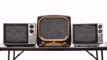 Three vintage televisions on white with dissolve to static and chroma green screens.