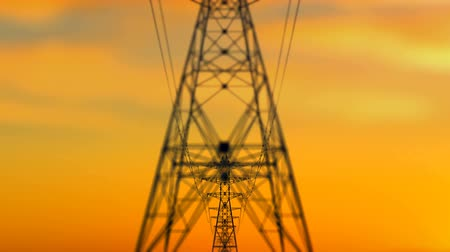 úgy néz ki : An arty 3d rendering of high cribriform electricity towers approaching quickly as a result of the dolly in effect. The background is dark yellow. It looks like a summer sunset. Stock mozgókép