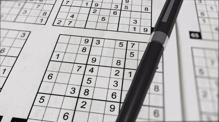 palavras cruzadas : An impressive pan looking 3d rendering of Sudoku mathematical networks with numbers, columns, rows and empty boxes placed aslant. A black pen lies on this puzzle. Stock Footage