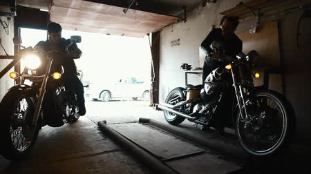 empurrando : Two bikers taking custom motorbikes to the garage
