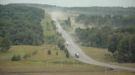 camionagem : Trucks traveling on a road between forests. Stock Footage