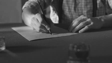 pergament : hand writing a letter or story with vintage quill and old pieces of paper