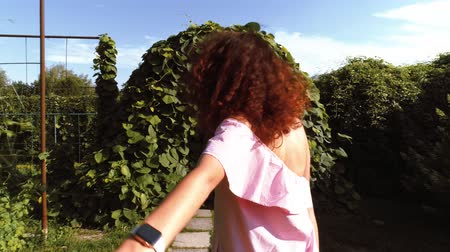 questão : Girl smiling and leading boyfriend walking in the garden Stock Footage