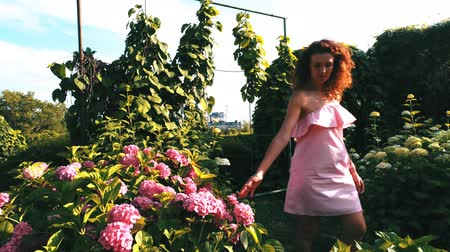 função : Young attractive woman walk near flowers and touch blooms in garden