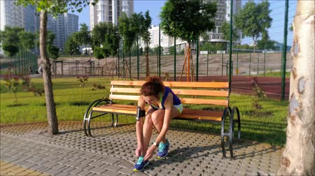бегун трусцой : Beautiful girl is sitting on the bench in the park, preparing to run