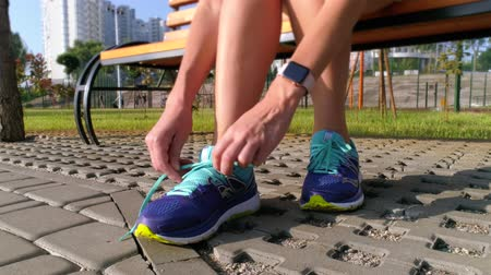 humanóide : Girl is sitting on a bench, preparing to run. Sportswearshoes close-up Stock Footage