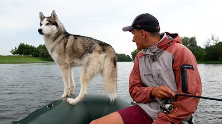 daleko : The fisherman is fishing on the river while sitting in a boat with the Husky