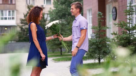 cheerfulness : Boyfriend giving buquet of white flowers to his girlfriend