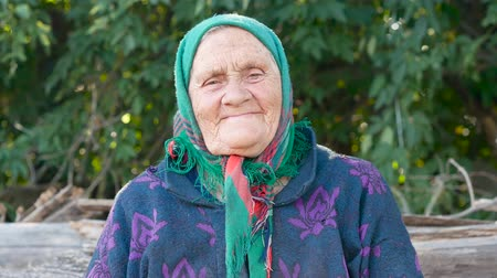 refrigeração : Grandmother in a green kerchief sits in the yard of the village and smiles. Close up