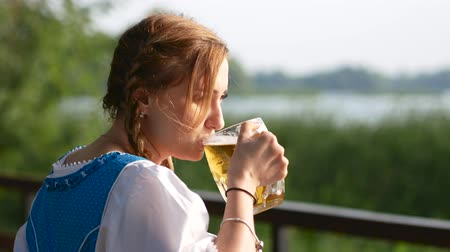 Октоберфест : The blond girl stands near the bridge and drinks beer. Close up Стоковые видеозаписи