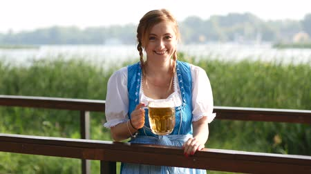 Октоберфест : Blond woman in blue bavarian costume drinks beer