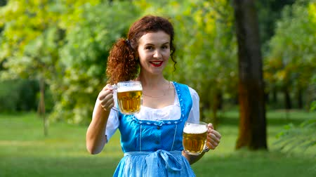 Октоберфест : Beautiful curvy haired woman with a glass of a beer. Oktoberfest theme. Medium shot Стоковые видеозаписи
