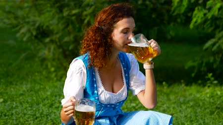 Октоберфест : Beautiful curvy haired woman drinks alcohol. Oktoberfest theme. Medium shot