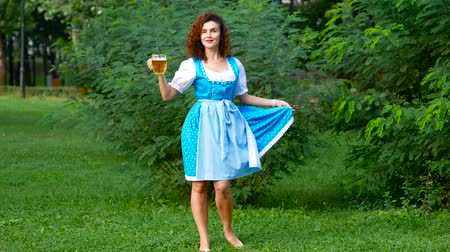Октоберфест : Attractive curvy haired woman in bavarian costume with beer. Oktoberfest theme. Overal shot