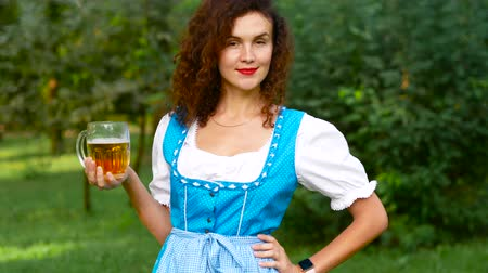 Октоберфест : Charmful curvy haired woman in bavarian costume with beer. Oktoberfest theme. Medium shot