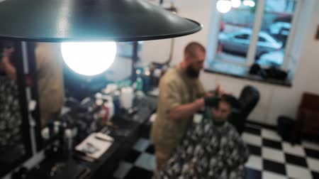 haircut : Master and his client are in the defocus. Lamp in the foreground. Overall plan Stock Footage