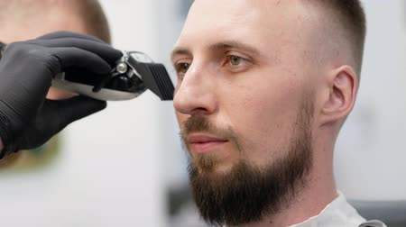 beard trimming : Portrait of a bearded man at the barbershop Stock Footage