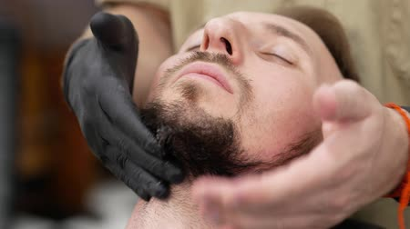 esvoaçantes : Male customer is receiving a massage on his beard with an after shave lotion by an hairstylist Stock Footage
