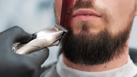 shaver : Barber is cutting the clients using red comb and electric shaver