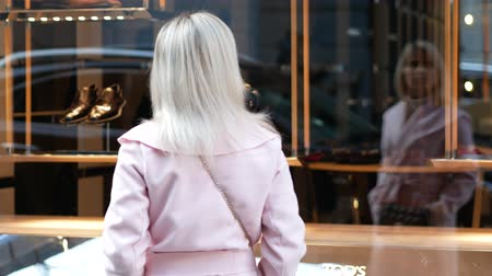 şey : Young woman in pink coat looking for desired thing at boutique window Stok Video