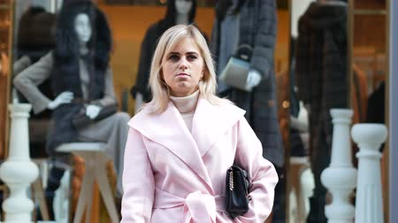 papieros : Beautiful blonde girl in pink coat smokes against the closing store. Middle shot Wideo