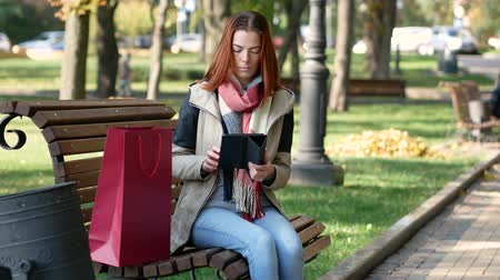 тачпад : Modern student with red hair sitting on a bench and using the tab. Early autumn