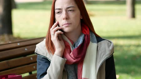 uzakta bakıyor : Young girl with red hair talks with someone by phone while sitting on a bench Stok Video