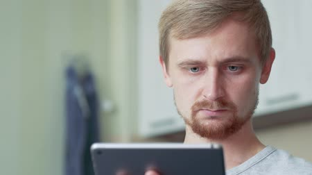 šatník : Handsome ginger guy sitting in the kitchen and using his ipad
