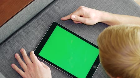 dragging : Young blonde man uses tablet with green screen while lying on sofa at home