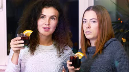 mulled wine : Young women at home party, drink mulled wine and enjoy carefree time. Pastime indoors concept.