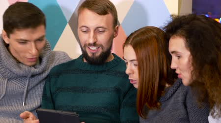 навынос : Group of people enjoy carefree time. Beardy guy shows his ipad, everybody sit with open mouths. Celebration concept