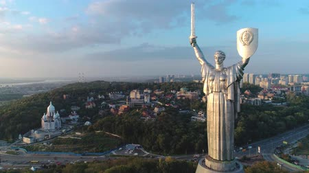 kard : Aerial shot. Soviet-era monumental statue Motherland Mother with a shield and sword in the capital of Ukraine, Kiev. Early sunset. Overall plan Stock mozgókép