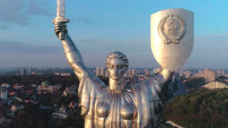 kard : Aerial shot. Soviet-era monumental statue Motherland Mother with a shield and sword in the capital of Ukraine, Kiev. Early sunset. Dolly zoom