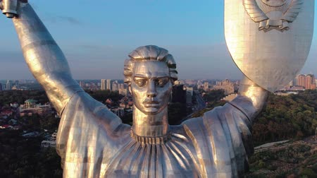 мемориал : Aerial shot. Soviet-era monumental statue Motherland Mother with a shield and sword in the capital of Ukraine, Kiev. Early sunset. Middle plan