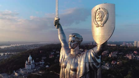 kard : Aerial shot. Soviet-era monumental statue Motherland Mother with a shield and sword in the capital of Ukraine, Kiev. Early sunset. Middle plan