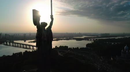 kard : Aerial shot. Soviet-era monumental statue Motherland Mother with a shield and sword in the capital of Ukraine, Kiev. Silhouette against the sunset. Overall plan Stock mozgókép