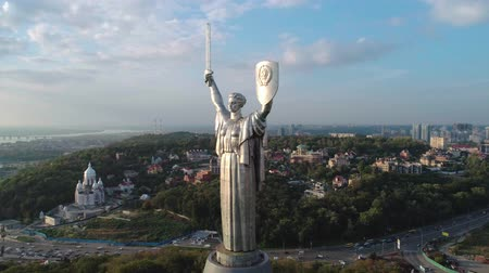 kard : Aerial shot. Seagulls fly over soviet-era monumental statue Motherland Mother with a shield and sword in the capital of Ukraine, Kiev. Early sunset. Overall plan