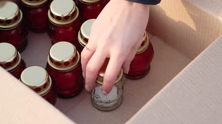 надгробная плита : Womans hand takes red votive candle out of the cardboard box. Mourning concept. Close up