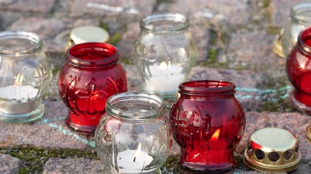 deceased : Red and white grave candles burn on the ground. Mourning concept. Close up
