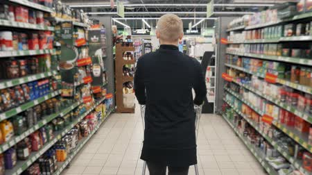 troli : Young man in black clothes walks in a grocery store. Shelves with products on the sides Stock mozgókép