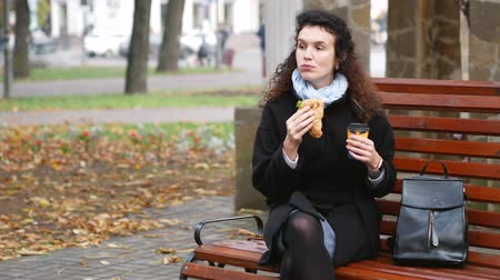 prejudicial : Brunette eats croissant and drinks coffee outdoors at lunchtime. Office employee at lunch concept Stock Footage